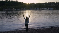 Young Woman Stands Close To Water And Raises Her Arms In Air, Makes Peace Signs Stock Footage
