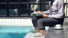 Young businessman working with documents sitting by pool in outdoor villa Stock Footage