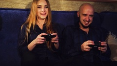 Funny girl and a guy are playing computer games Stock Footage