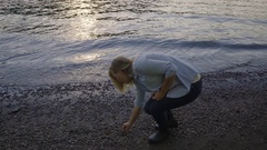 Young Woman Looks For And Gathers Stones At Water's Edge Stock Footage