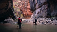 Photographers standing in the Zion Narrows taking photos Stock Footage