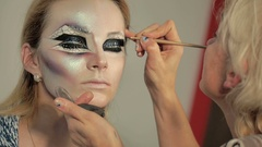 The woman the master of makeup makes a woman sophisticated makeup Stock Footage