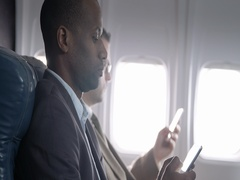 First class airline passengers using mobile devices on commercial flight 4K Stock Footage