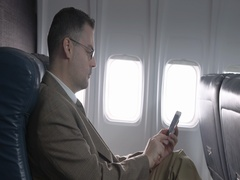 First class airline passenger listening to call on cellphone 4K Stock Footage