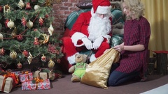 Girl steals a gift from Santa's bag Stock Footage