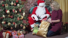 Jolly Santa looks in the bag with gifts surprised girl Stock Footage
