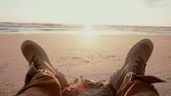 A close up of two feet in brown boots resting on a sandy beach at dawn Stock Footage