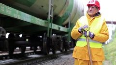 Railway worker in yellow uniform with shovel in hands stands near railway line Stock Footage
