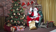 Santa waving his hand while sitting in a chair at the Christmas tree Stock Footage