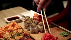 Man sits at the table in restaurant and eats japanese food Stock Footage