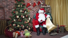 Santa collecting gifts in a bag sitting in a chair at the Christmas tree Stock Footage
