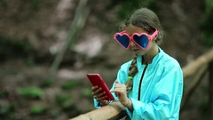 Girl in big sunglasses in the shape of hearts makes selfie on his smartphone Stock Footage