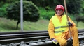 Railway worker in yellow uniform with shovel in hand sits on railway line HD Footage