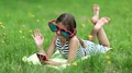 Pretty girl in big sunglasses with red smartphone lies on green grass HD Footage