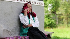 Old woman sits near grey wall of his house and talks on cell phone Stock Footage