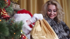 Closeup girl with snow-white smile stares at Santa with a bag of gifts Stock Footage