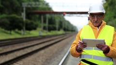 Railway worker makes notes in his tablet computer Stock Footage
