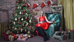 Sexy girl sitting in a chair near a Christmas tree Stock Footage