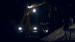 Excavator bucket scoops up earth from the hole and pours out. Night excavating Stock Footage