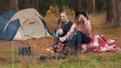 Two girlscook marshmallow at campfire. They smile and have fun Autumn forest. Stock Footage