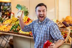 Man jokes with leek and red pepper in hands. Stock Photos