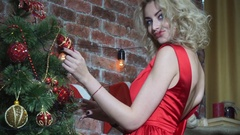 Closeup, seductive blonde girl playing with a toy on the Christmas tree Stock Footage