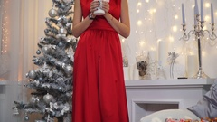 Girl in a long red dress with big lips and seductive eyes blowing a candle Stock Footage