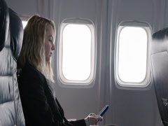 Young woman using cellphone in first class section of aircraft 4K Stock Footage
