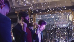 Attractive young men partying in the night club in confetti. A group of young Stock Footage