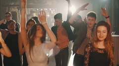 Close up view of young stylish company dancing and jumping on the dance floor in Stock Footage