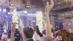 Delicate female hands cheering in the air the musical band in golden confetti Stock Footage