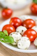 Tomatoes and Mozzarella with fresh Basil (selective focus) on an old wooden tabl Stock Photos