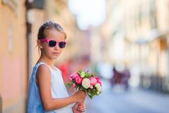 Adorable little girl with flowers bouquet walking in european city Stock Photos