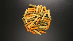 TOP VIEW: Colorful fusilli pastas shake on a black table (stop motion) Stock Footage