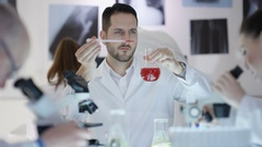 4K Portrait smiling research scientist working in the lab with colleagues Stock Footage