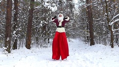 Dancing of Santa Claus on the stilts in the snowy forest at slow motion. Stock Footage