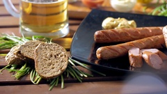 Dressing bratwurst with mustard during a breakfast. Warm and tasty mood. Stock Footage