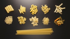 TOP VIEW: Several pasta types fill on a black table (stop motion) Stock Footage