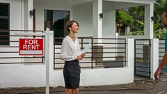 Female estate agent shaking happy man's hand near new home and sign For Rent Stock Footage