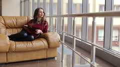 Deluxe girl sits in a leather chair with a tablet and listening to the music. Stock Footage