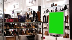 Green billboard for your ad beside shoes store with people buying new shoes Stock Footage