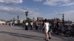 Small number of people stroll at Patriarshy Bridge, panoramic camera turn left Stock Footage