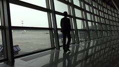 One man come along glass wall at empty airport lounge, full length view Stock Footage