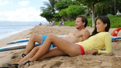 Two people relaxing after surfing with surfboards at beach Arkistovideo