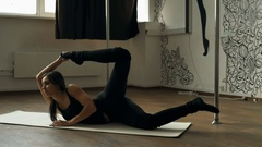 Very flexible woman stretching on an exercise mat during a workout Stock Footage