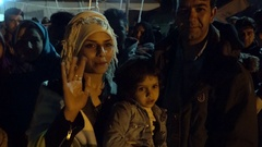 LESVOS, GREECE - NOV 5, 2015: Afghan refugee family in the queue for the bus to Stock Footage