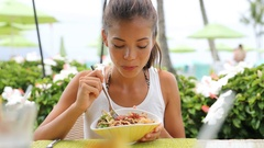 Asian woman eating hawaiian food tuna poke bowl Stock Footage