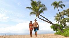 Hawaii holiday couple walking on Maui beach Stock Footage