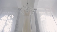 Wedding white dress hanging on chandelier inside space room Stock Footage