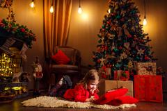 Little girl lying in carpet with presents around using tablet on red pillow Stock Photos